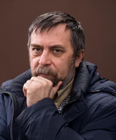 Portret van een oudere man op een bruine achtergrond