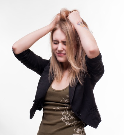 Young woman suffering from headache on a white background