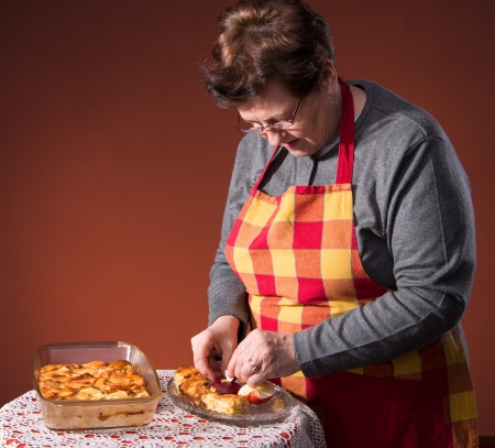 Mature woman serving apple pie on an orange background Stock Photo - 18442253