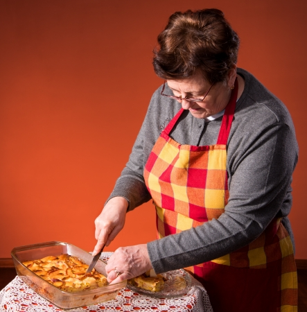 Mature woman cutting apple pie on an orange background Stock Photo - 18442247