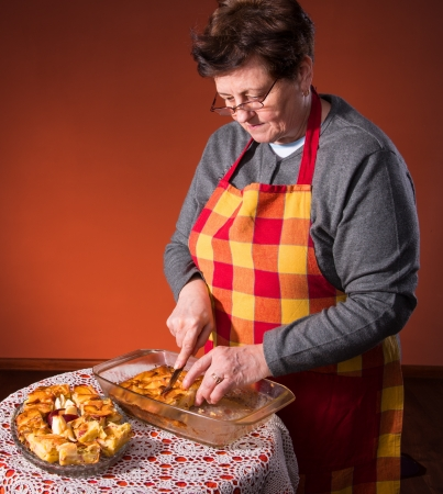 Mature woman cutting apple pie on an orange background photo