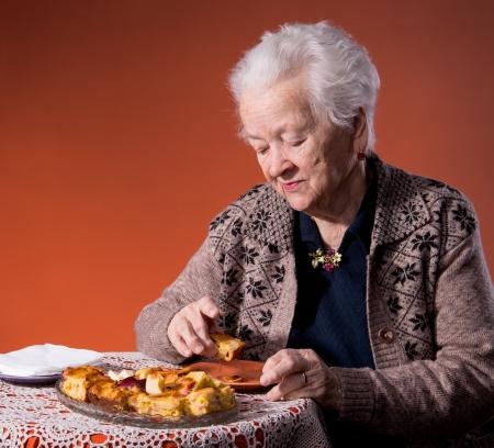 Senior woman tasting apple pie on an orange background Stock Photo - 18473092