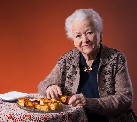Senior woman tasting apple pie on an orange background Stock Photo - 18473093