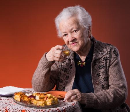 Senior woman tasting apple pie on an orange background Stock Photo - 18442268