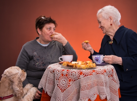 Mother and daughter having tea with apple pie on an orange  background photo