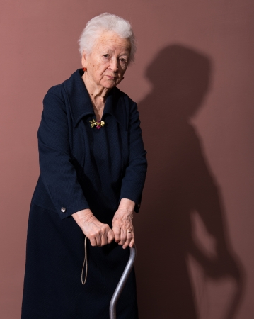 fine cane: Old woman with a cane on brown background Stock Photo