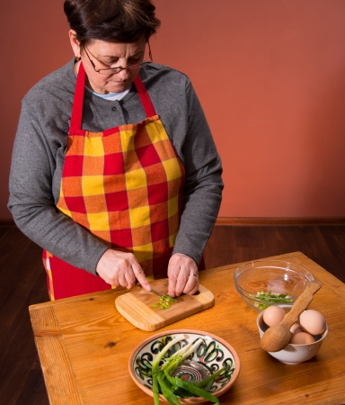 Woman preparing salad  on an orange background Stock Photo - 18434962