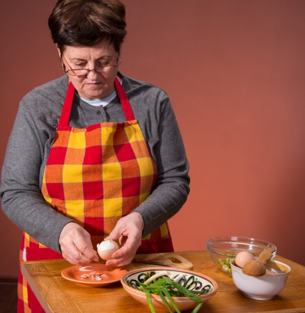 Woman preparing salad  on an orange background Stock Photo - 18434963