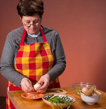 Woman preparing salad  on an orange background Stock Photo - 18434963