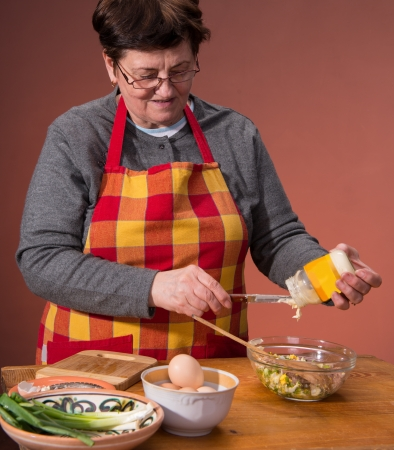 Woman preparing salad  on an orange background Stock Photo - 18434944