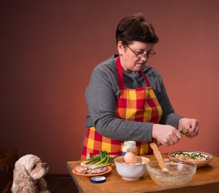 Woman preparing salad  on an orange background Stock Photo - 18442240