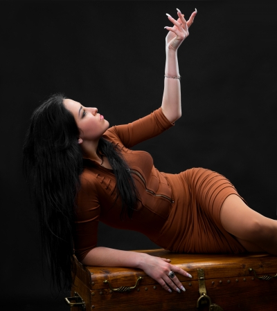Sexy woman laying on a wooden chest on a gray background Stock Photo - 18574100