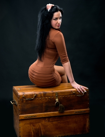 Sexy woman sitting on a wooden chest on a gray background Stock Photo - 18574208