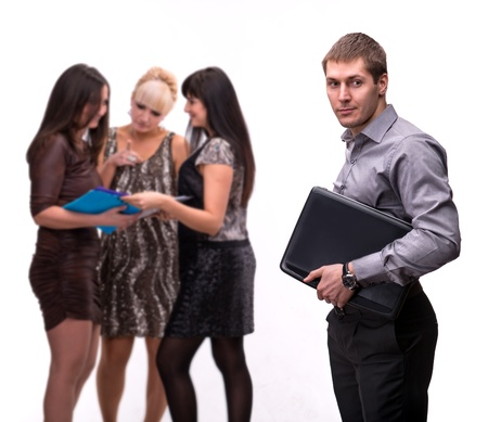 Portrait of young man with laptop with group of people talking in background