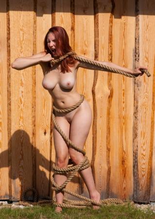 corps femme nue: jeune femme nue avec une corde autour du corps sur un fond en bois Banque d'images