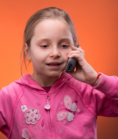 Girl talking on a cell phone on an orange background photo