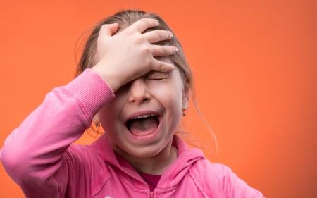 niño llorando: sobre un fondo naranja Foto de archivo