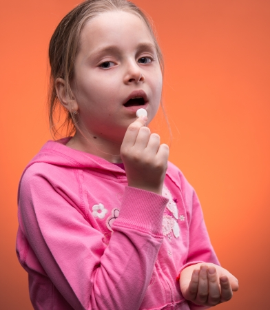 Girl taking pill on an orange background Stock Photo - 18687558