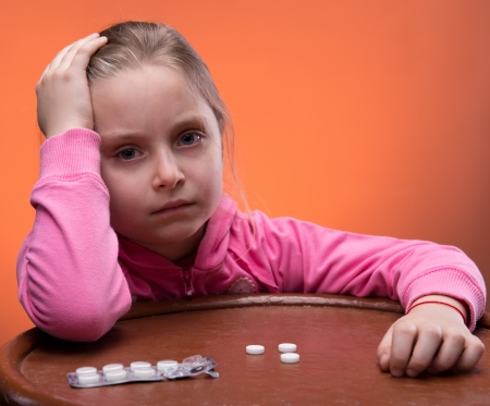 Little girl looks very upset at the thought of taking her medicine photo