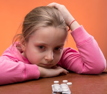 little table: Little girl looks very upset at the thought of taking her medicine