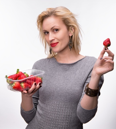 Young happy blond girl with fresh strawberries on a white background photo