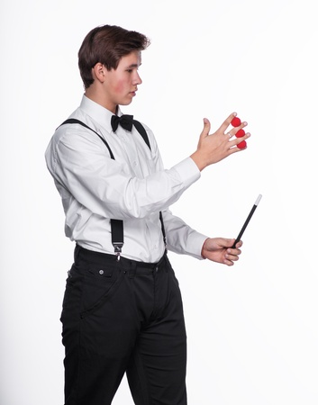 A magician holding  magic balls and wand on a white background