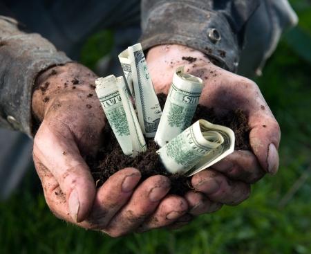 Farmer holding soil with dollars photo