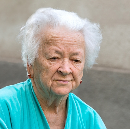 Old sad woman on a gray background Stock Photo