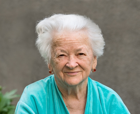 Portrait of smiling old woman on a gray background photo