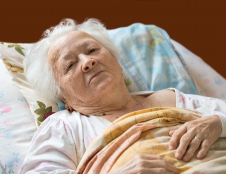malade au lit: Senior femme pose au lit