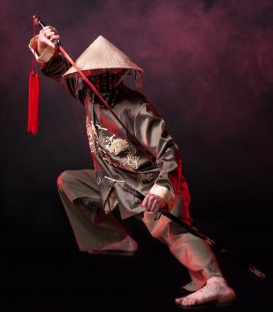 Aziatische krijger in conische hoed met swards