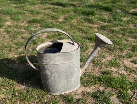 watering pot: Aged metallic watering pot full of water on natural background   Stock Photo