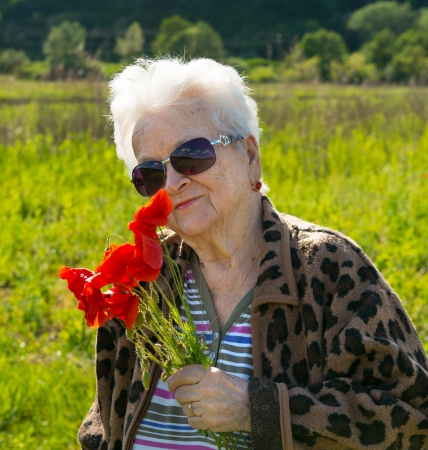 Old woman in sunglasses with bunch of poppies photo