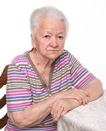 Portrait of old sad woman on a white background