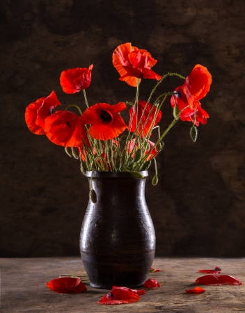 Bunch of poppies in vase on a wooden background
