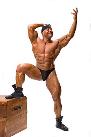 Bodybuilder stellen dichtbij houten kist op een witte achtergrond