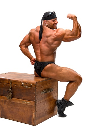 pectorals: Bodybuilder sitting on a wooden chest ona white background Stock Photo