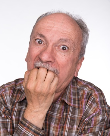 Portrait of a very surprised elderly men with a fist in his mouth 免版税图像