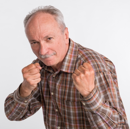 Mature man in boxer pose with raised fists on a white background photo