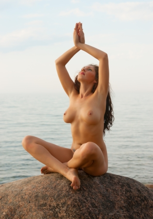 Naked Yoga. Young nude woman sitting on stone on sea background