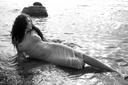 nue plage: Belle femme dans un maillot de bain se trouvant dans l'eau � la plage