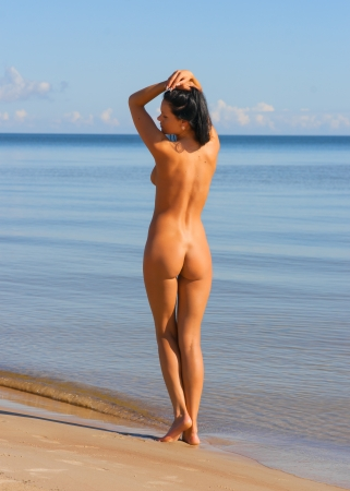 beach breast: Beautiful young naked woman sunbathing on the beach