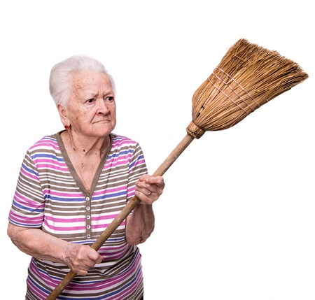 Old angry woman threatening with a broom on a white background 免版税图像
