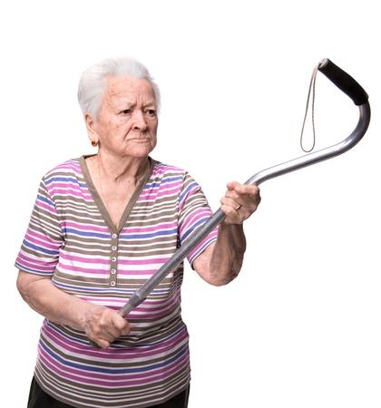 Oude boze vrouw bedreigt met een stok op een witte achtergrond