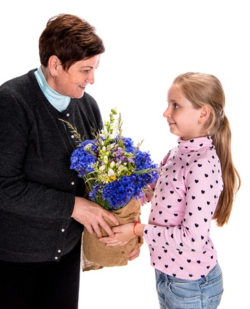 Granddaughter presenting bouquet of  wildflowers to her grandmother on a white background  photo