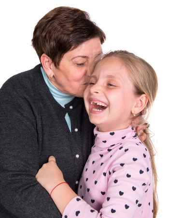 Grandmother kissing happy granddaughter on a white background photo