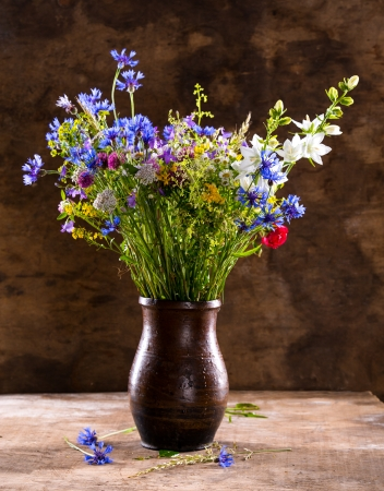 Beautiful bouquet of bright wildflowers in vase on a wooden background photo