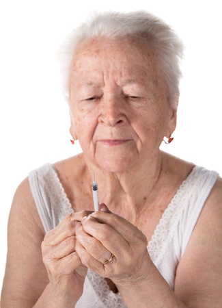 Old  woman preparing syringe for making insulin injection on a white background photo