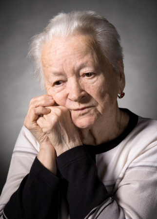 Old  thoughtful woman on a gray background photo