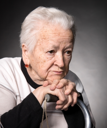 Portrait of old woman sitting with a cane on a gray background photo